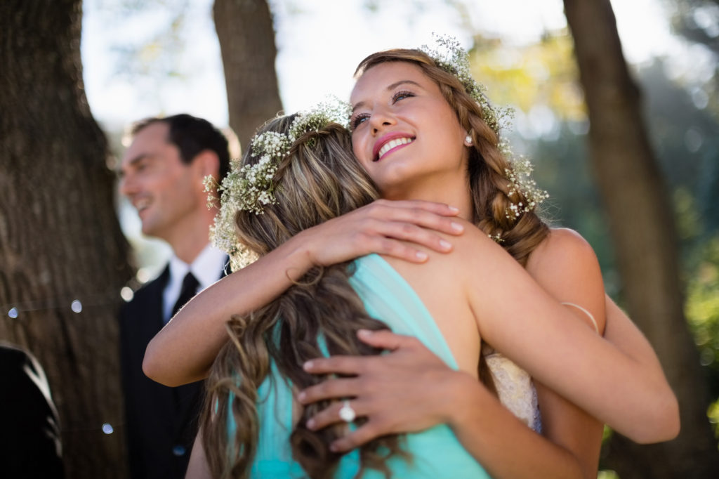 Bride embracing her friend in park during wedding